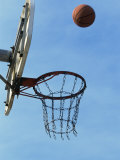 Low Angle View of a Basketball Bouncing Off The Hoop Photographic Print