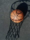 Close-up of a Basketball Resting on The Shadow of a Basketball Hoop Photographie