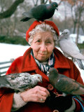Birds Perched on Mature Woman Sitting in Park Photographic Print by Paul Katz