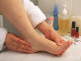 Woman Massaging Foot After Bath Photographic Print by Gary Conner