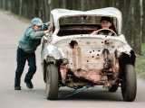 A Boy Pushes an Abandoned and Damaged Car as Another Boy Steers It Photographic Print