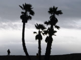 A Man Looks out Towards the Ocean as a Winter Rain Storm Falls on Seal Beach Photographic Print