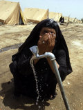 A Woman Washes Her Face with Water from a Tap at a Camp for Displaced Iraqis Photographic Print