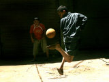 An Egyptian Boy Shows off His Ball Skill as He Plays Soccer with a Friend on the Steets of Cairo Photographic Print