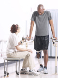 Physical Therapist Assisting Patient on Parallel Bars Photographic Print