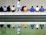 With the Water Reflection, a Muslim Man Walks Past Others Offering the Friday Prayer at a Mosque Photographic Print