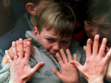 A Father's Hands Press against the Window of a Bus Carrying His Tearful Son and Wife to Safety Photographic Print