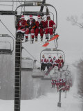 Skiers and Snowboarders Dressed as Santa Claus Ride up the Ski Lift Lámina fotográfica