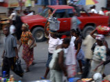 An Water Vendor Walks in the Streets of Port-Au-Prince, Haiti Photographic Print