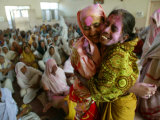 Two Indian Women, with Festive Colored Powder on Their Faces, Embrace and Dance Lmina fotogrfica