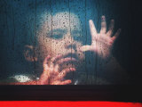 A Young Indonesian Boy Chases Raindrops on the Back Window of a Passenger Bus Photographic Print