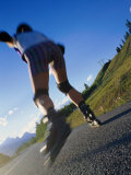 Woman Roller-Blading Along Mountain Road, Canada Photographic Print by Philip Smith