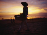 A Snack and Cigarette Vendor in a Straw Hat on the Beach at Dusk Photographic Print