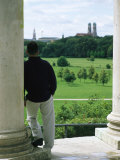 A Man Stands Looking at the English Garden in Munich Photographic Print by Taylor S. Kennedy
