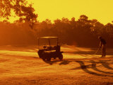 Man and Golf Cart Silhouetted at Sunset Photographic Print by Bill Bachmann