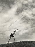 Young Boy Atop a Hill Hurls a Javelin into the Air Photographie