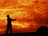 Man Swinging Golf Club at Sunset Fotografie-Druck von Bill Bachmann