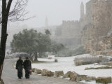 Two Priests Walk in Snow in Front of the Jaffa Gate in Jerusalem's Old City, December 27, 2006 Photographic Print by Oded Balilty