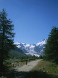 A Couple Walks Toward the Morteratsch Glacier in Switzerland Photographic Print by Taylor S. Kennedy