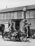 Motor Cycle Rider Stops at a Garage in Scotland for Petrol Sitting Photographic Print