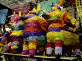 Several Brightly-Colored Pinatas Await Buyers in a Mexican Market Photographic Print by Stephen St. John