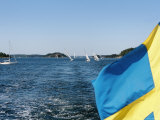 Swedish Flag with Sailboats in the Background, Stockholm Archipelago, Sweden Reprodukcja zdjęcia