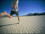 A Man Runs Barefoot Across the Desert in Death Valley Photographic Print by Kate Thompson