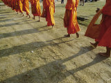 Buddhist Monks Walk Single File Down a Dirt Road Photographic Print by Jodi Cobb