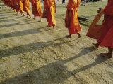 Buddhist Monks Walk Single File Down a Dirt Road Photographic Print by Jodi Cobb