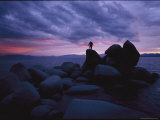 A Man Stands on a Large Rock Jutting out into the Harbor Photographic Print by George F. Mobley