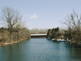 Snow and Bare Winter Trees Surround a Covered Bridge Photographic Print by Stephen St. John