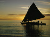 Silhouetted Outrigger Canoe on the Koro Sea Photographic Print by Thomas J. Abercrombie