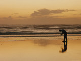 A Man Examines a Shell on the Beach at Sunset Photographic Print by Emory Kristof