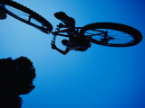 A Mountain Biker Careens in the Air and the Photographer Captures This Dynamic Image from Beneath Photographic Print by Barry Tessman