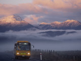 Bus at Sunrise with the Mountains Covered in a Blanket of Fog Photographic Print by Annie Griffiths