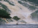 A Man on a Canoe Near the Crashing Waters of Kongou Falls Photographic Print by Michael Nichols