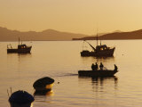 Fishing Boats Sit at Anchor While Another Boat Moves Slowly By Photographic Print by Annie Griffiths