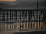 A Surfer Walks up the Beach Near a Pier at Twilight Photographic Print