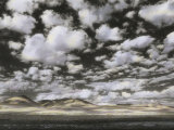 Puffy Clouds Fill a Sky Above Gentle Rolling Hills in the Distance Photographic Print by Annie Griffiths