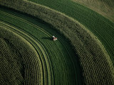 Aerial View of a Tractor on Curved Fields Fotografisk tryk af Paul Chesley
