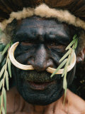 Elaborate Headdress and Boar Tusks Decorate the Face of a Tribesman Photographic Print