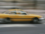 A Yellow Taxi Rushes by on a Busy New York Street Photographic Print by Roy Gumpel