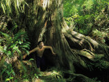 A Shirtless Man Emerges from the Hollow Trunk of a Tree Photographic Print by Joel Sartore