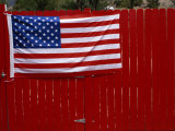 A United States Flag Hangs on a Bright Red Fence Fotodruck von Raul Touzon