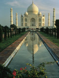 The Taj Mahal with a reflection of the tomb on  the surface of a pool Photographie par Ed George