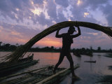 A Silhouetted Burmese Man Unloads Rattan from a Canoe Photographic Print