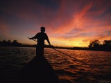 A Silhouetted Burmese Man Poling a Canoe at Sunset Photographic Print