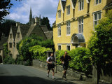 Hikers Jog Along a Street in the Village of Castle Coombe Photographic Print by Joel Sartore