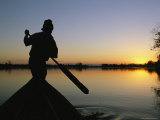 A Silhouetted Burmese Man in a Canoe at Sunset Photographic Print