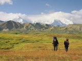 Man and Woman with Backpacks and Walking Sticks Cross Meadow Photographic Print by Mark Cosslett
